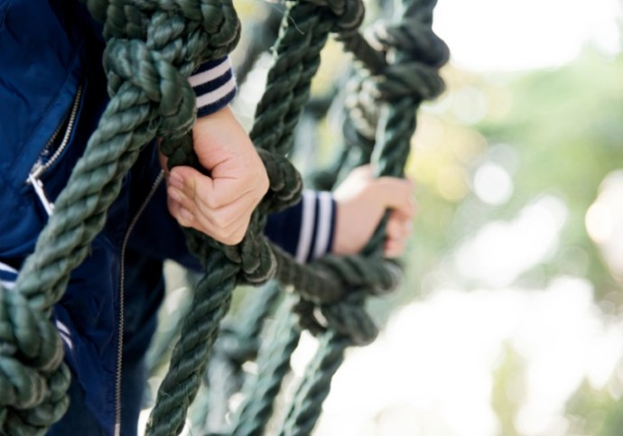 Little asian boy climbing outdoors rope frame.