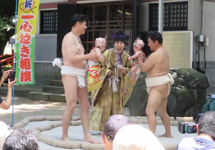 力士に抱っこされて土俵の上へ。伝統行事「泣き相撲」