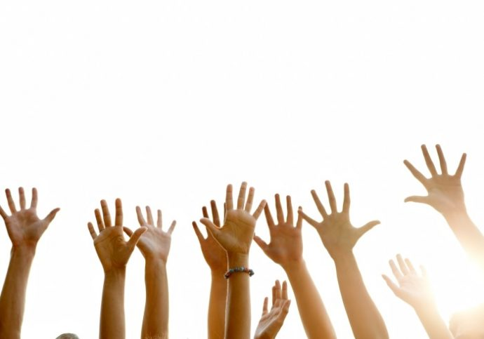 Raised arms of people against white background
