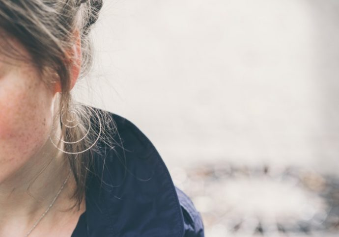Beautiful woman face portrait freckles street city. Outdoor shot.