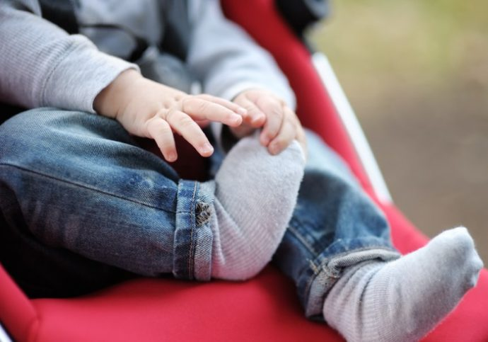 Little baby boy in stroller playing with his sock