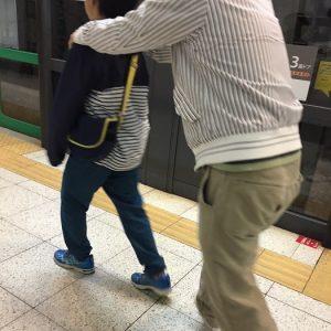 肉離れ中の父に肩を貸す息子。