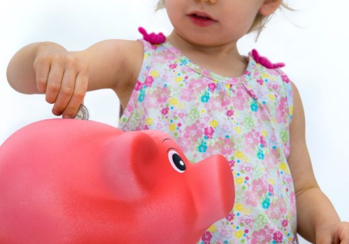Two-year old girl throwing money into piggy bank. Shallow depth of field.