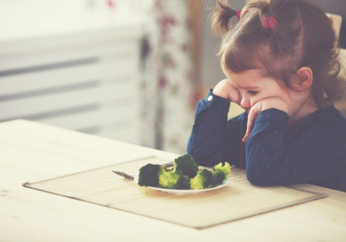 child girl does not like and does not want to eat vegetables