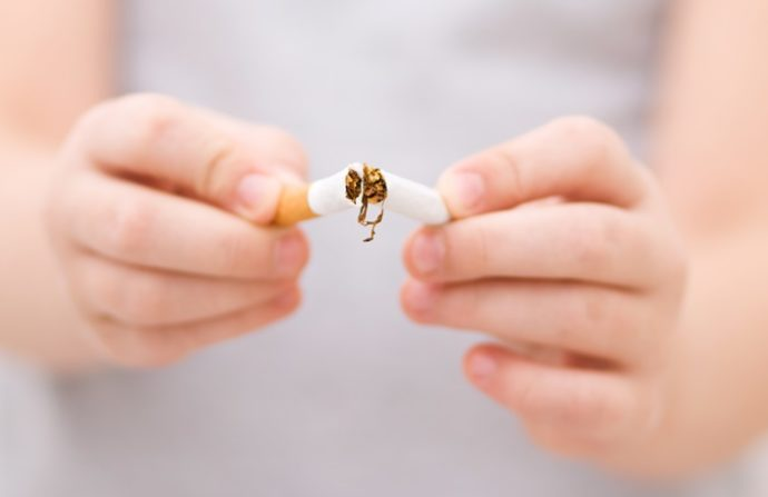 Young girl is breaking a cigarette, quit smoking concept