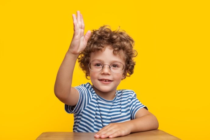 Cute young smart boy in glasses looking at camera with hand up.