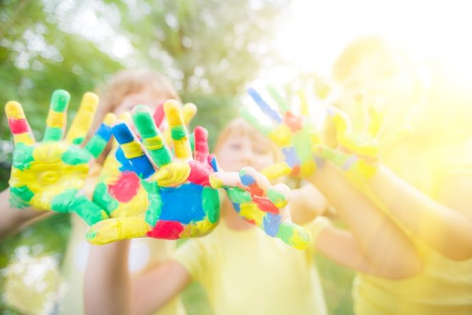Group of friends with painted hands against green spring background