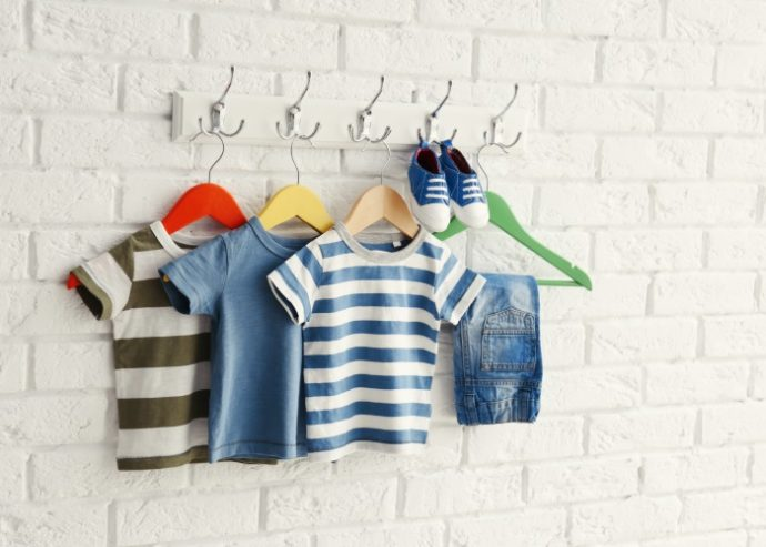 Set of baby clothes on brick wall background