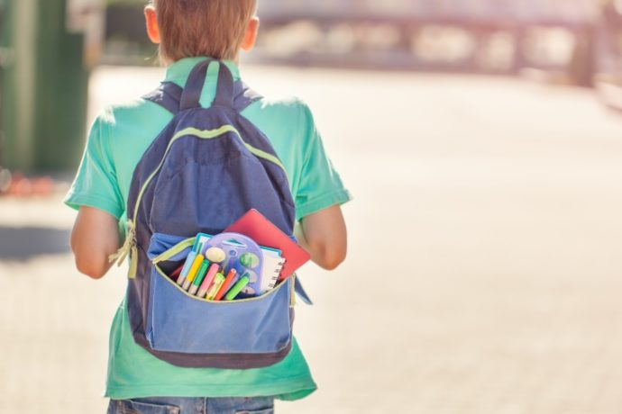 Schoolboy with full backpack go to school. Back view.