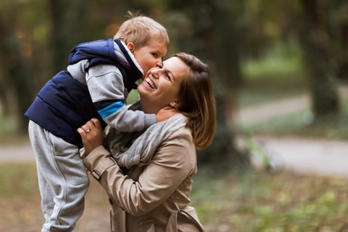 Happy mother and child smiling outdoors