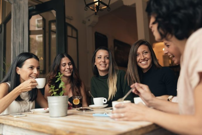 Six beautiful women drinking coffee and chatting in cafe