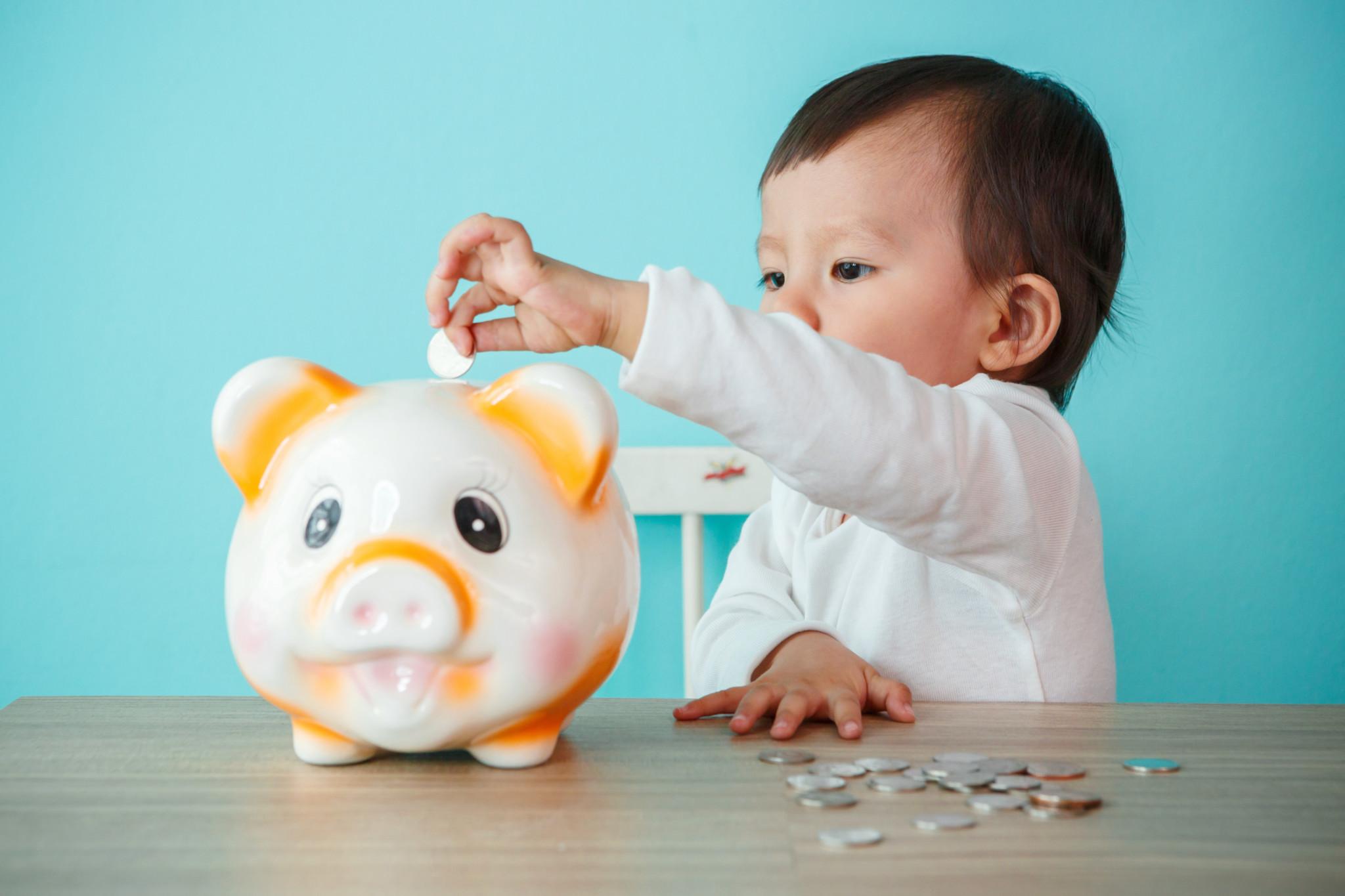 little baby moneybox putting a coin into a piggy bank – kid savi