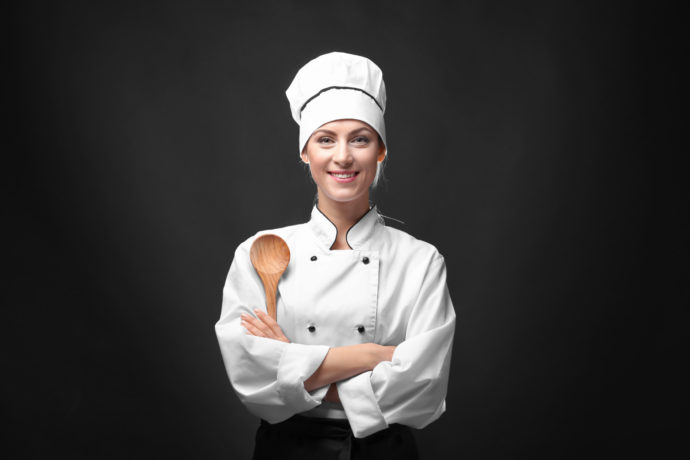 Portrait of female chef with wooden spoon on dark background