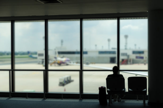 silhouette of business tourist people with luggage looking at airplanes and waiting at the plane boarding gates before departure in airport, travel, lifestyle and transportation concept