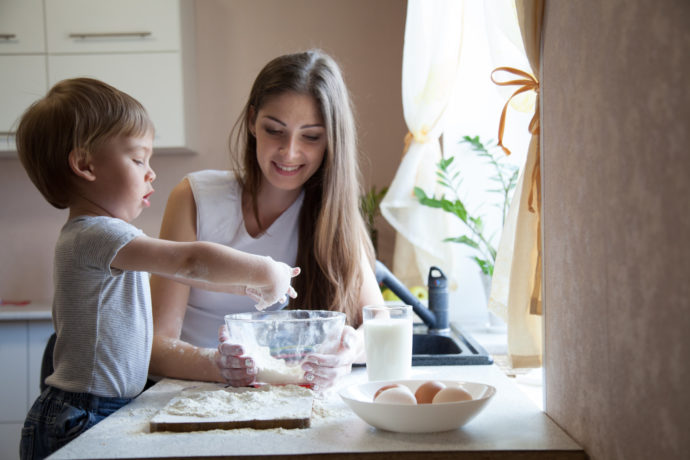 mother and son prepare pie with flour