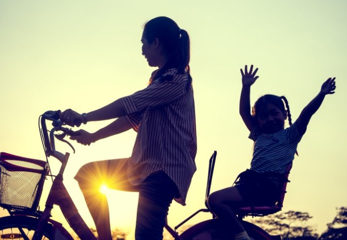 Happy family concpet, Mother and daughter riding a bicycle at sunset