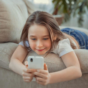 Leisure, children, technology and people concept - Beautiful little girl with smartphone.