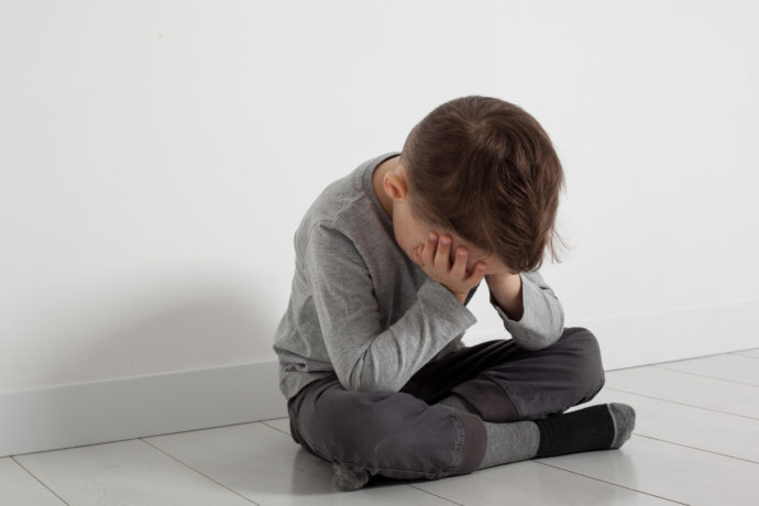 a child whose depression is sitting on the floor