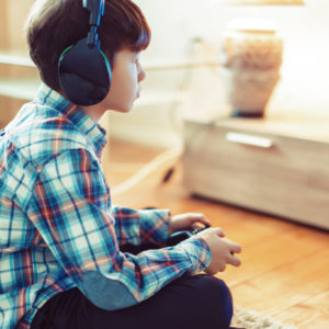 Little boy playing video game by controller at home side view