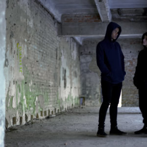 Boys in hoodie talking in ruined building, teenage gang, young criminals