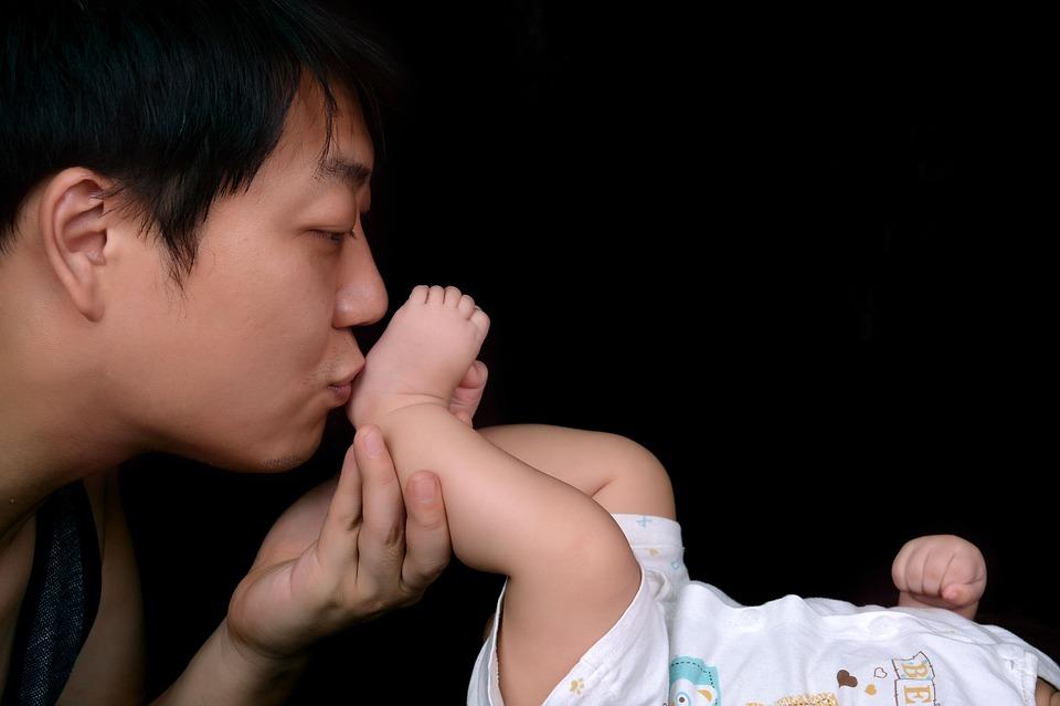 赤ちゃんの足にキスをするパパ