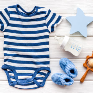 Blue bodysuit for baby boy near children's accessories on white wooden background top-down.