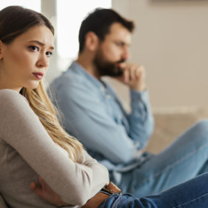 Worried young woman sitting on sofa at home and ignoring her boyfriend who is sitting next to her