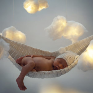 Cute little baby sleeping in the hammock with a lot clouds made of cotton wool