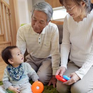 リビングで孫のお世話をする祖父母