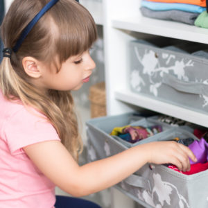 Cute European little girl with blond hair brings wardrobe order puts everything in its place hides things in boxes