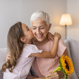 Cute girl giving a bunch of flowers to her grandmother. Happy senior grandma hugging granddaughter thanking for gift and flowers. Little granddaughter kissing giving flowers bouquet congratulating smiling old grandmother