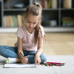 Concentrated little girl sit on floor in living room drawing in album with colorful pencils, focused small preschooler child relax in living room painting, engaged in favorite hobby activity at home
