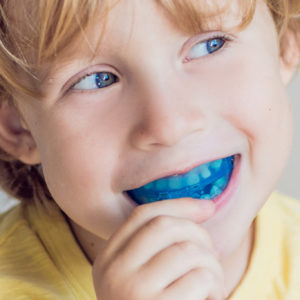 Three-year old boy shows myofunctional trainer to illuminate mouth breathing habit. Helps equalize the growing teeth and correct bite. Corrects the position of the tongue. BANNER, long format