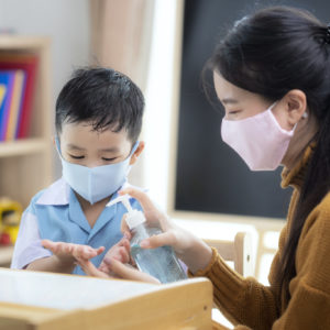 Asian woman teacher use alcohol gel on hand of her student for prevent virus from covid19 in classroom in preschool.