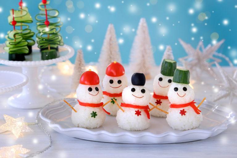 ミニトマトやきゅうりやオリーブの帽子をかぶったおにぎりでできた雪だるま
