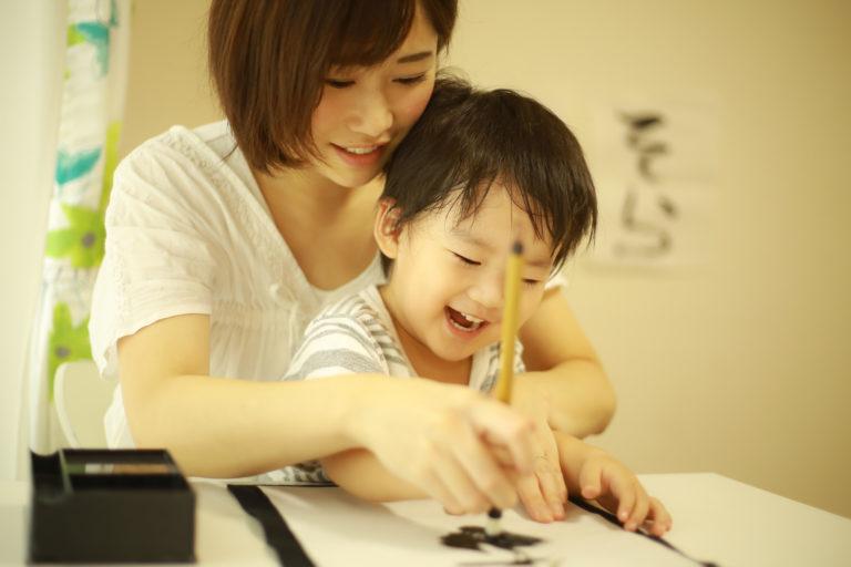 書き初めをする母親と子供