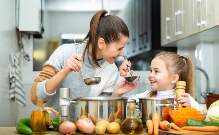 楽しそうに料理をし味見する母と娘