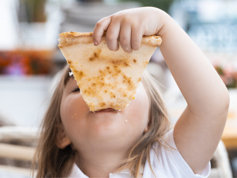A young girl with plaits is eating a piece of pizza