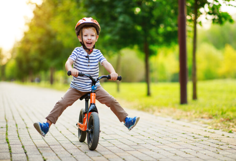 happy child boy rides a racetrack in Park in the summer