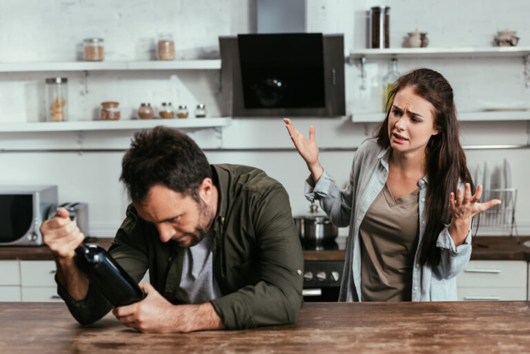 Worried woman quarreling on alcohol addicted husband with wine bottle on kitchen