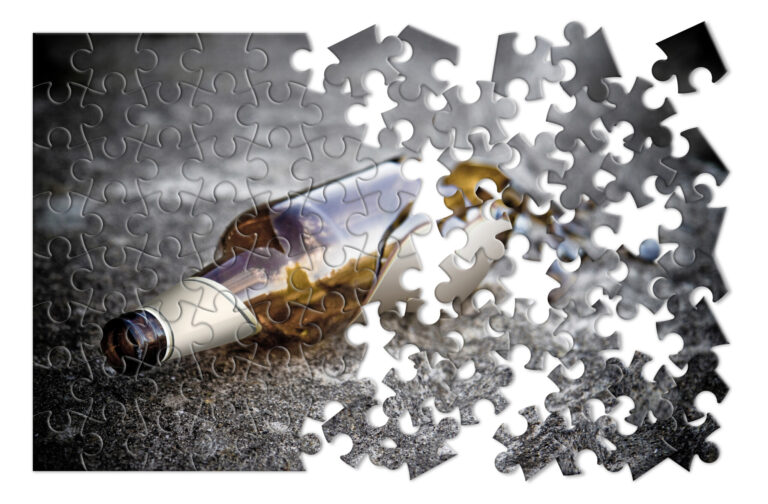 Puzzle of a broken bottle of beer resting on the ground - Free themselves from alcohol addiction - concept image - Toned image