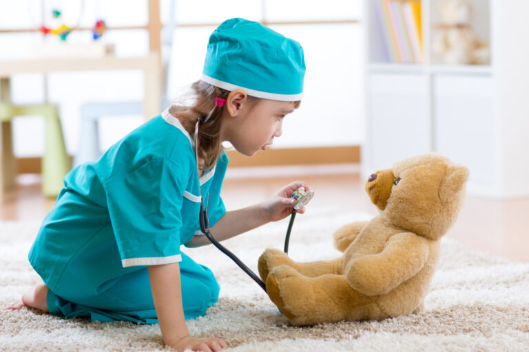 Funny child girl playing with teddy bear and pretending she is a doctor in hospital