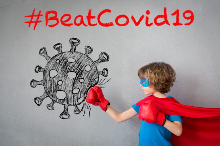 Superhero child beat COVID-19. Super hero kid punching on the drawn coronavirus. Winner and success concept