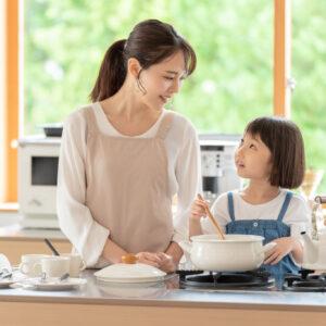 台所で料理を作るお母さんと女の子