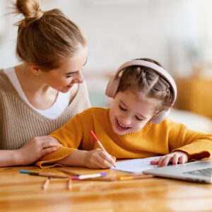 Cheerful little schoolgirl in headphones writing exercises in copybook while studying remotely via laptop at home with happy mom sitting nearby and giving support
