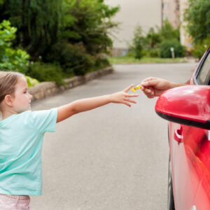Stranger in the car offers candy to the child. Kids in danger. Children safety protection. Children kidnapping concept.