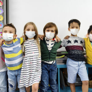 Kindergarten kids wearing masks in a classroom