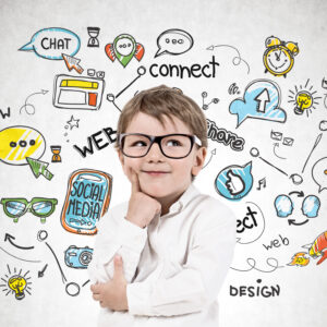 Smiling thinking little boy wearing white shirt and glasses standing near concrete wall with colorful social media sketch drawn on it.