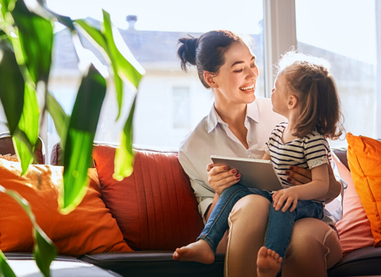 Young mother and her daughter girl play in kids room with tablet.