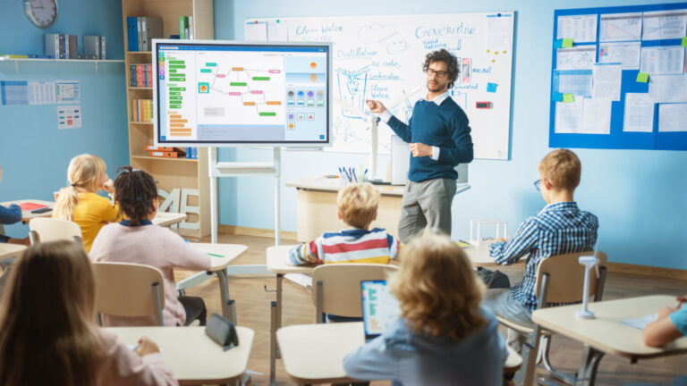 Elementary School Computer Science Teacher Uses Interactive Digital Whiteboard to Show Programming Logics to a Classroom full of Smart Diverse Children. Computer Class with Kids Listening